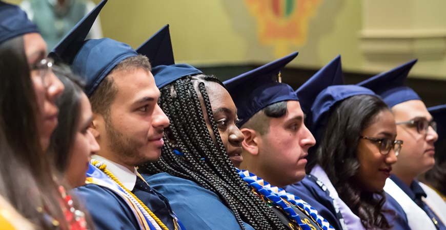 Graduating students listen to a speaker during commencement.